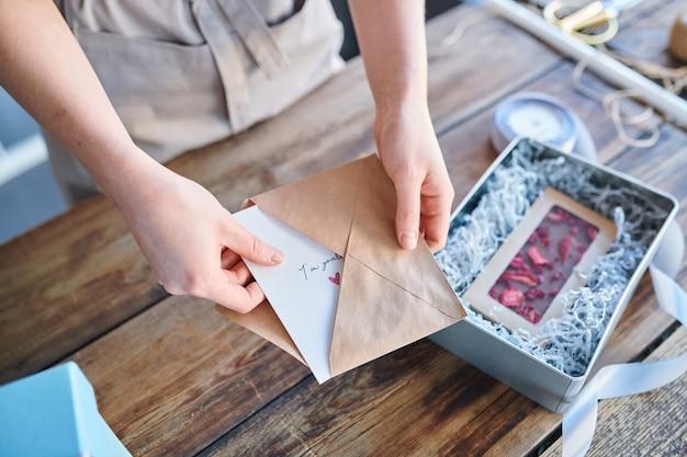 職場での贈り物を準備しながらバレンタイングリーティングカードを封筒に入れて若い女性