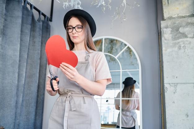 バレンタインの日の準備中に大きな赤い紙のハートとはさみを保持しているエプロンと帽子の若い女性