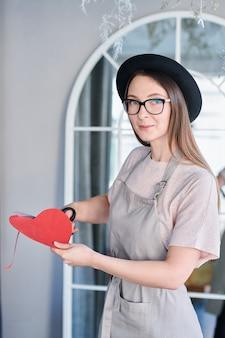 エプロンと帽子のスタジオでカメラの前に立っている間赤い紙のハートをカットでかわいい女の子