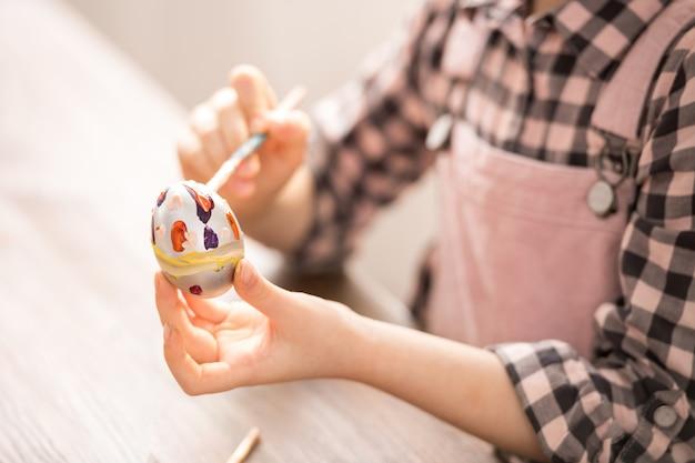 Девушка рисует пасхальное яйцо