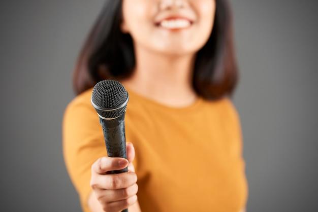 Женщина дает молодой микрофон