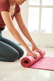 Женщина выкатывает коврик для йоги