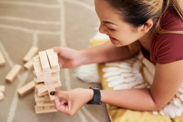 木製のブロックで遊んで元気な女性