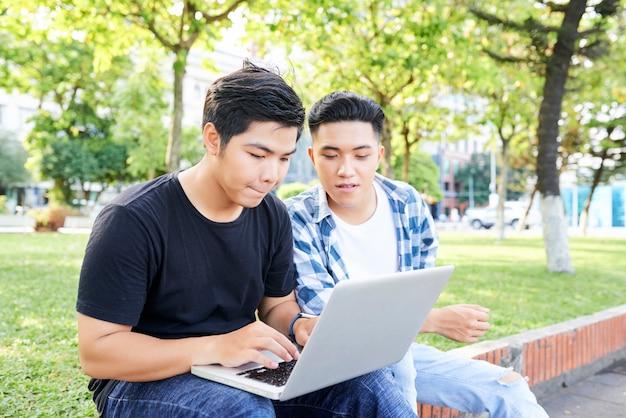 Студенты колледжа используют ноутбук на открытом воздухе