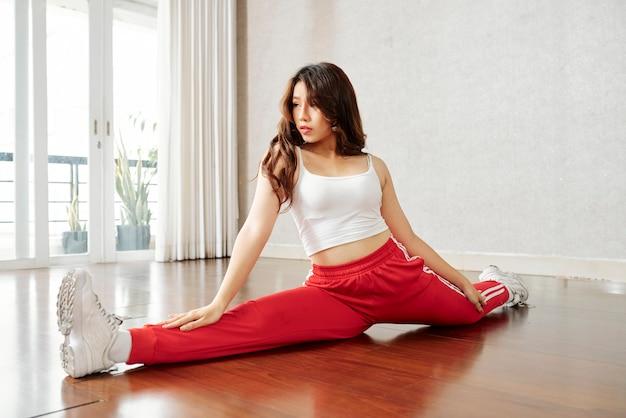 スプリットの練習スポーティな柔軟な女性