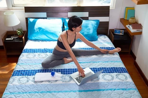 Женщина, используя ноутбук во время тренировки на дому