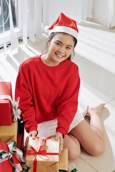 Девушка открывает рождественские подарки