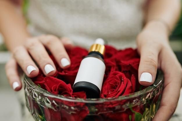 Женщина дает розовое масло