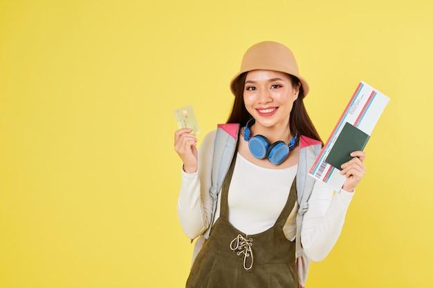 Милая женщина показывая билет на самолет и кредитную карту