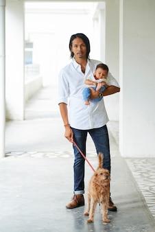 赤ちゃんと彼のペットと一緒に歩いている男