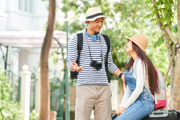 Молодая улыбающаяся пара обсуждает поездку