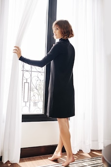 カーテンを開く裸足の若い女性
