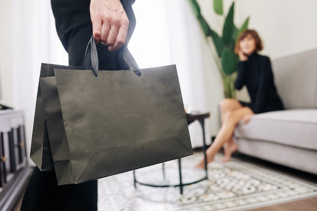 Мужчина приносит домой подарки для своей жены