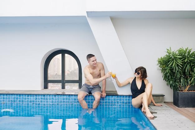Молодая пара пьет фруктовые коктейли у бассейна