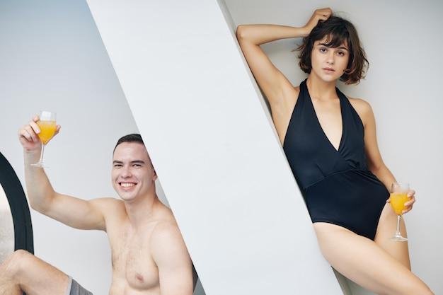 Красивая пара с коктейлями у бассейна