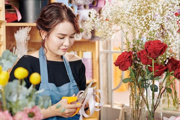 花束の若い花屋カッティングリボン