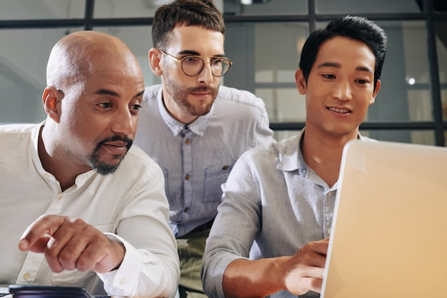 Бизнес команда собралась у открытого ноутбука