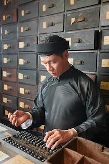 Работник аптеки делает расчеты со счетами