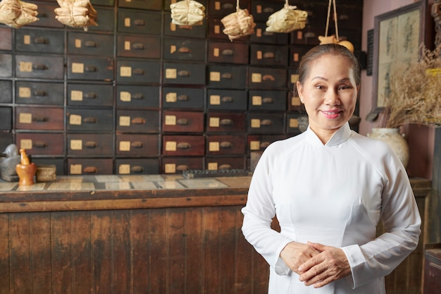 伝統的な中国の薬局で働く年配の女性