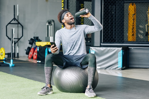 フィットネスボールの上に座ってのどが渇いてスポーツマン
