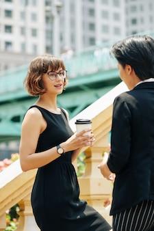 Деловая женщина с чашкой кофе разговаривает с коллегой