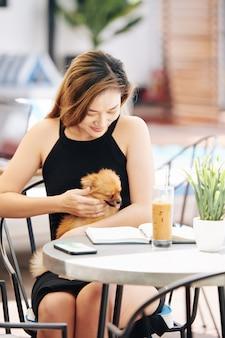 Молодая женщина гладит маленькую собаку