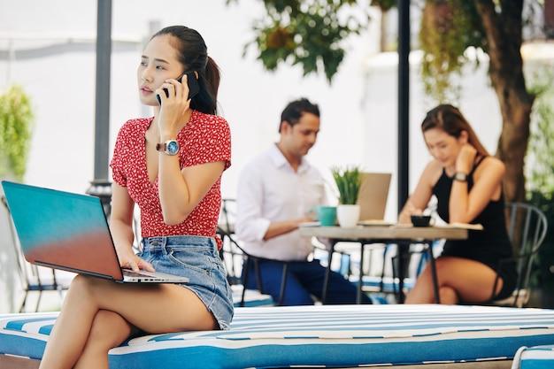 電話で話しているラップトップを持つ若い女