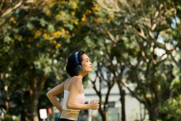 Подходящая женщина, бегающая трусцой в парке
