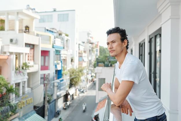 Задумчивый человек, стоящий на балконе