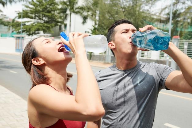 スポーティなカップルは水を飲む