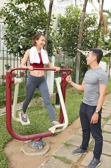 若い男が彼の運動のガールフレンドをやる気にさせる