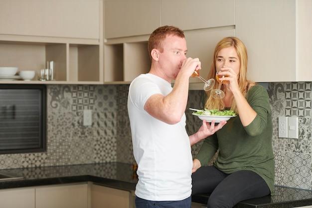 Пара наслаждается вином и салатом