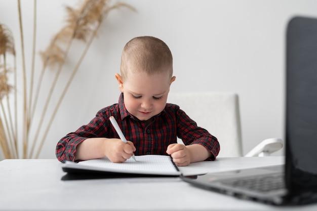 男子生徒が家で勉強しています。彼はオンラインで宿題をし、ノートに書き込みます
