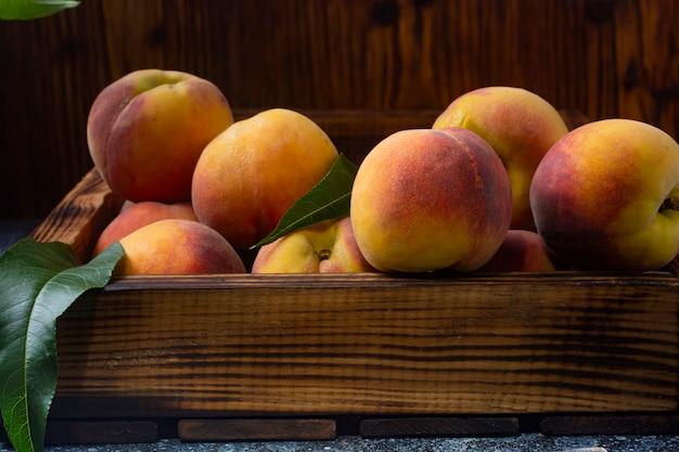 Персики в старой деревянной коробке крупным планом.
