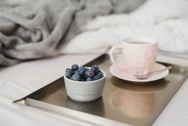 Чашка кофе и свежей черники подается на металлическом подносе. завтрак в постель