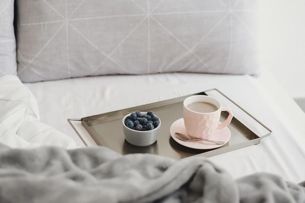 Кофе и черника на металлическом подносе служили в постели. легкий утренний завтрак