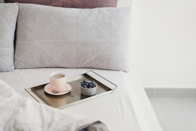 Кофе и свежая черника на металлическом подносе подаются в постели