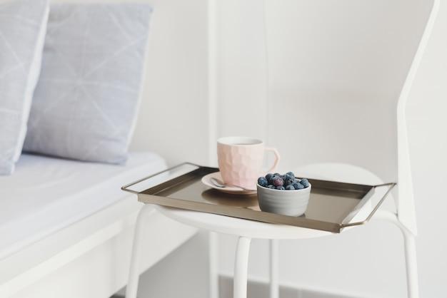 Легкий завтрак подается на металлическом подносе. кофе в розовой чашке и свежая черника на белом стуле