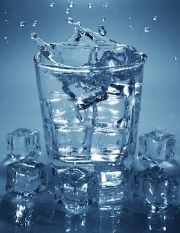 Лить кубик льда в стакан воды. брызги воды.