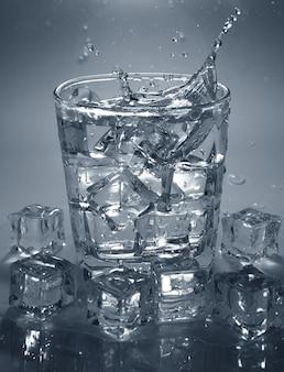 氷を飲み物のコップ一杯の水に注ぐ。水しぶき