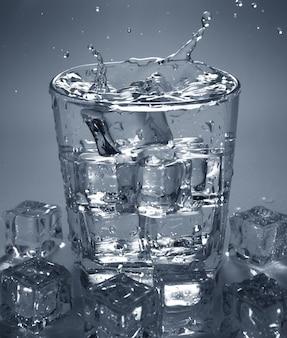 アイスキューブを水の入ったガラスに注ぐ。水の飛沫。