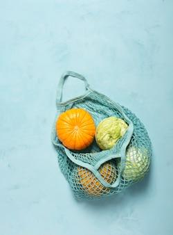 水色の表面に環境に優しいメッシュの新鮮な野菜