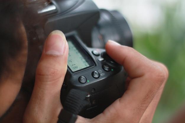 カメラのデジタル一眼レフカメラを使用している人の手