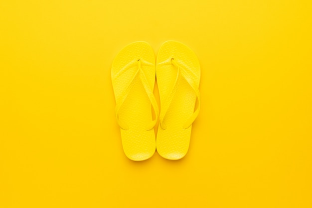 Желтые пляжные шлепанцы на желтом фоне