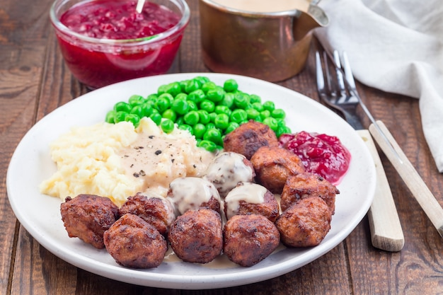 Традиционные шведские фрикадельки с картофельным пюре, зеленым горошком, сливочным соусом и клюквенным джемом