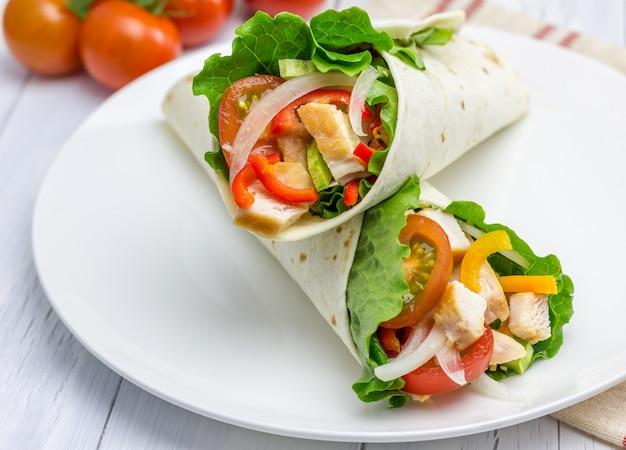 Тортилла обертывания с жареным куриным филе, свежими овощами и соусом на белой тарелке