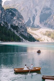 イタリアのラーゴディブレイエスで木製ボートでセーリング結婚式のカップル。ヨーロッパ、ブロイエス湖、ドロミテの新婚夫婦