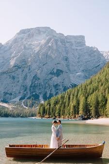 イタリアのラーゴディブレイエスで木製ボートで新郎新婦。ヨーロッパ、ブロイエス湖、ドロミテの結婚式のカップル