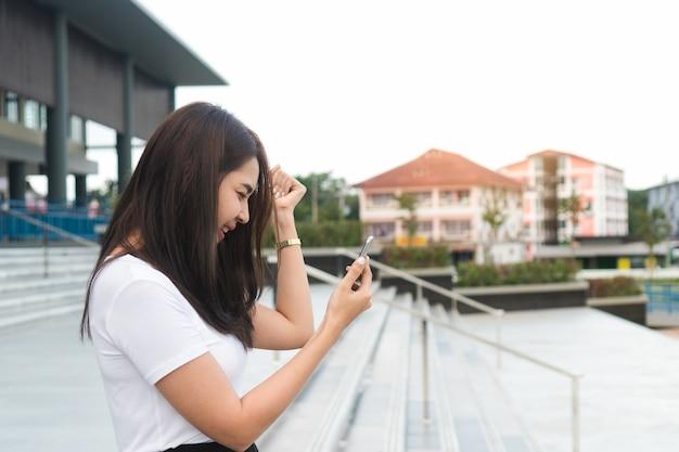 携帯電話で良いニュースを読む叫んだ若いアジアの女性の学生を興奮。