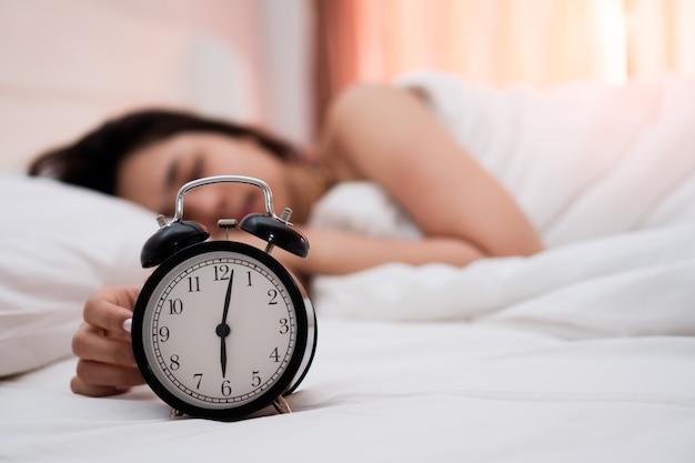 美しい若い女性が寝室の白いベッドで静かに眠っている目覚まし時計。